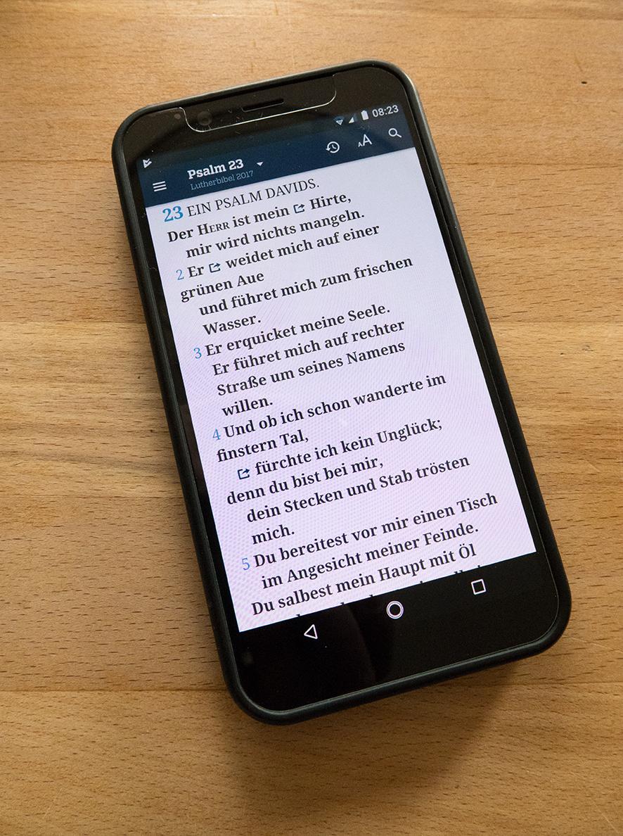 """Ein Handy, auf dem Psalm 23 zu lesen ist: """"De Herr ist mein Hirte ..."""""""
