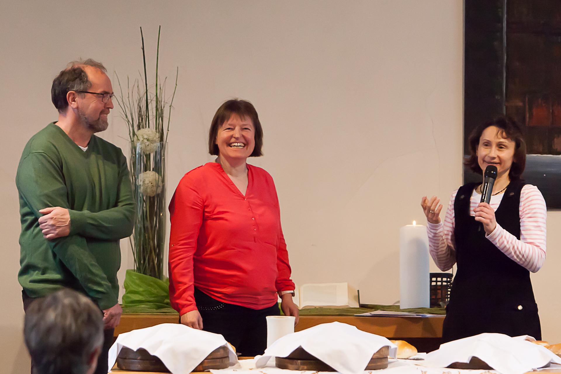 drei Personen, eine hält ein Mikrofon, die anderen lachen