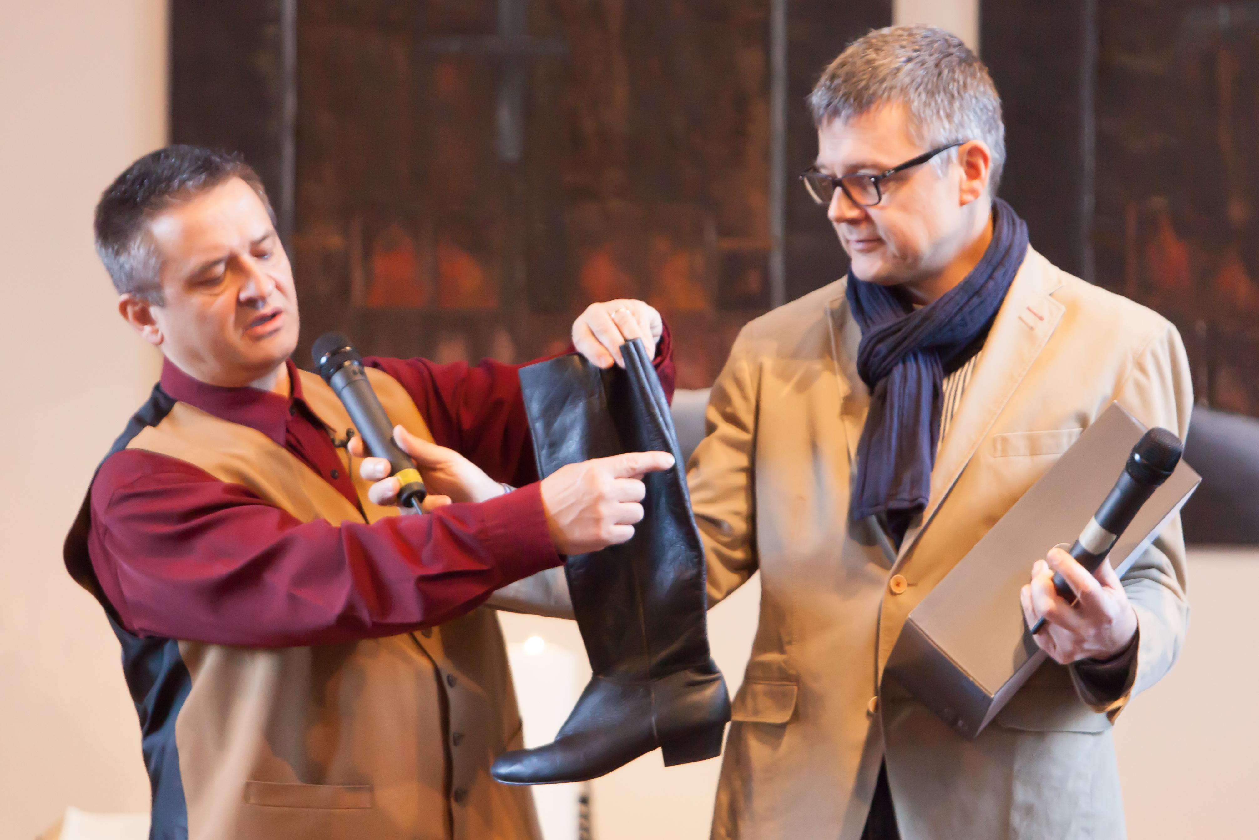 zwei Männer, einer hält einen Stiefel, zeigt mit Finger auf eine Stelle